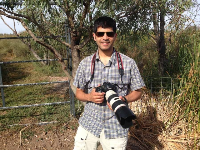 Aniket Sardana holding his camera near some trees and tall grass
