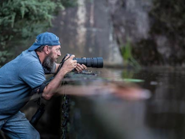 Peter Rowland waiting to take a picture of a Platypus with his camera