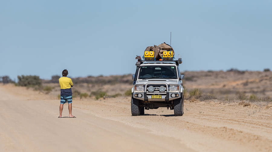 A man and a 4WD on a dirt road