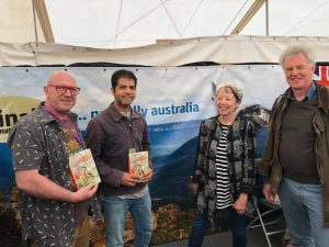 Peter Rowland, Aniket Sardana, Rosemary Wilkinson and John Beaufoy posing for a group photo at the Australia stall at Birdfair UK, holding a copy of the Australia's Birdwatching Megaspots book